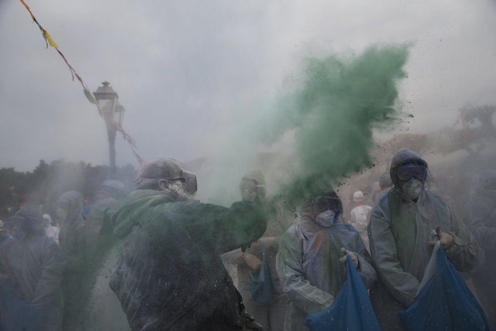 In this Monday, Feb. 19, 2018 photo, revelers throw flour as they take part in the flour war, a unique colorful flour fight marking the end of the carnival season in the port town of Galaxidi, some 200 kilometers (120 miles) west of Athens.  (AP Photo/Petros Giannakouris)