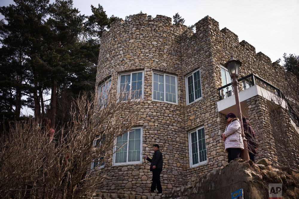 Visitors stand outside the villa known as Hwajinpo Castle, once a holiday home for late North Korea founder Kim Il Sung, at Hwajinpo Beach, South Korea, Monday, Feb. 19, 2018. (AP Photo/Jae C. Hong)