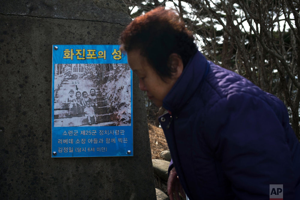 A visitor walks past a poster showing a childhood picture of Kim Jong Il taken when he was six at the villa known as Hwajinpo Castle, once a holiday home for late North Korea founder Kim Il Sung, at Hwajinpo Beach, South Korea, Monday, Feb. 19, 2018. (AP Photo/Jae C. Hong)