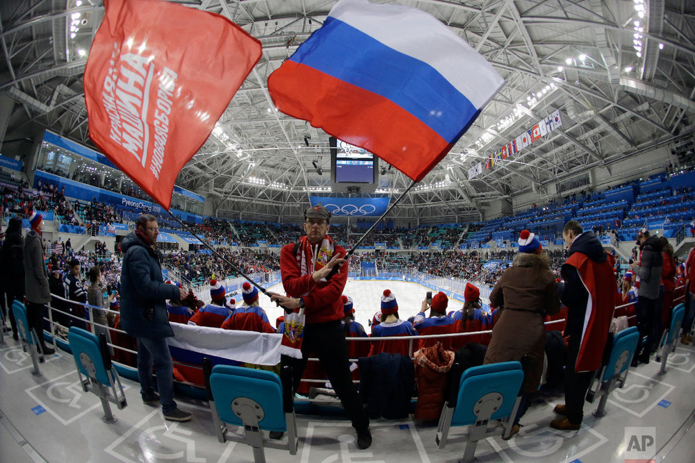 A fan of Russian athletes waves flags before the preliminary round of the men's hockey game between the team from Russia and the United States at the 2018 Winter Olympics in Gangneung, South Korea, Saturday, Feb. 17, 2018. (AP Photo/Julio Cortez)