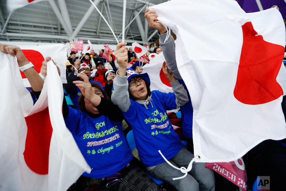Spectators wave the national flag of Japan during the women's 1,000 meters speedskating race at the Gangneung Oval at the 2018 Winter Olympics in Gangneung, South Korea, Wednesday, Feb. 14, 2018. (AP Photo/John Locher)