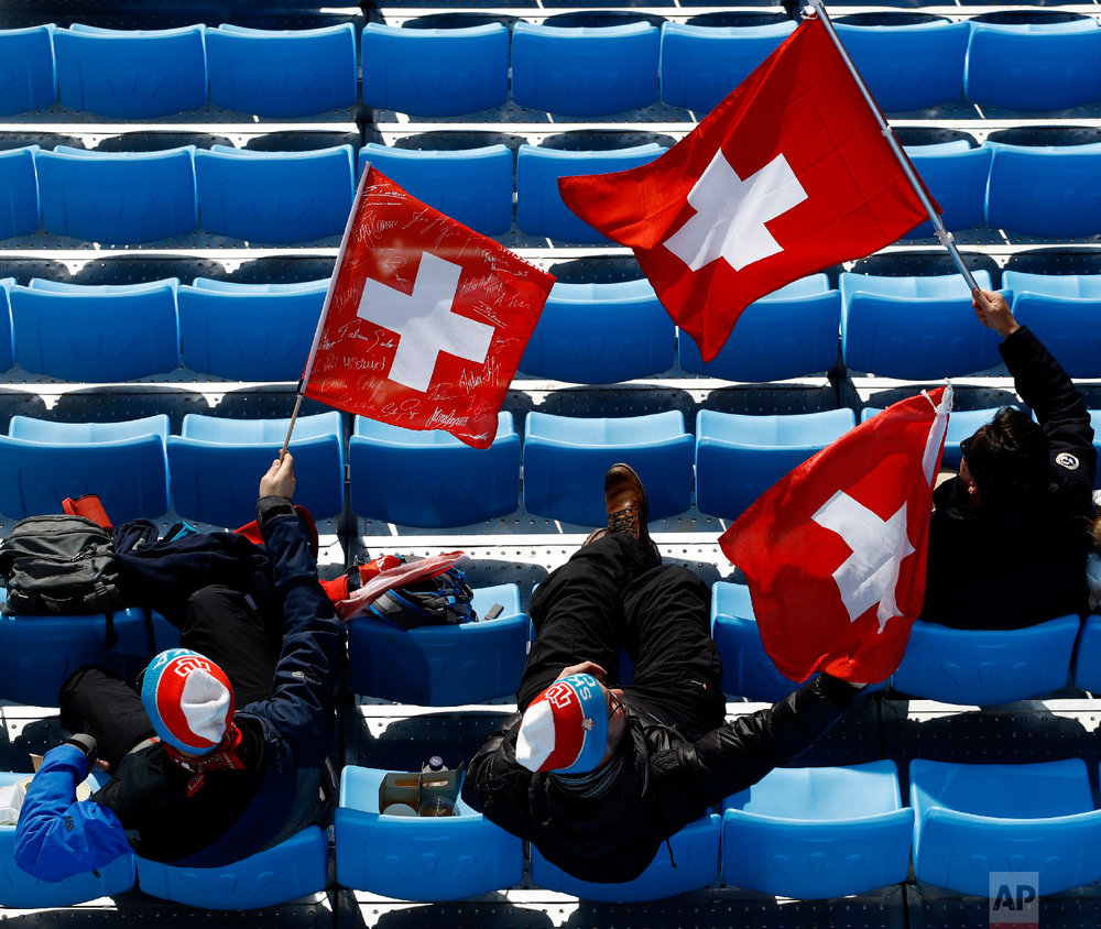 Fans wave Swiss flags as they watch the men's downhill at the 2018 Winter Olympics in Jeongseon, South Korea, Thursday, Feb. 15, 2018. (AP Photo/Charlie Riedel)