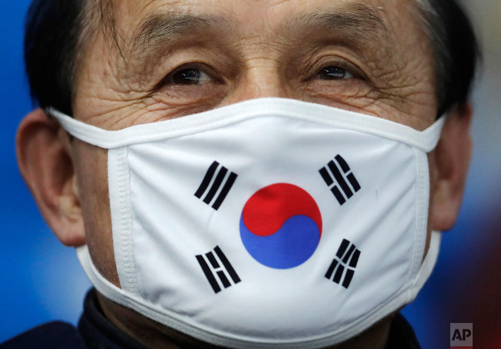A spectators wears a protective mask with the South Korean flag as he waits for the start of the men's 10,000 meters speedskating race at the Gangneung Oval at the 2018 Winter Olympics in Gangneung, South Korea, Thursday, Feb. 15, 2018. (AP Photo/Petr David Josek)