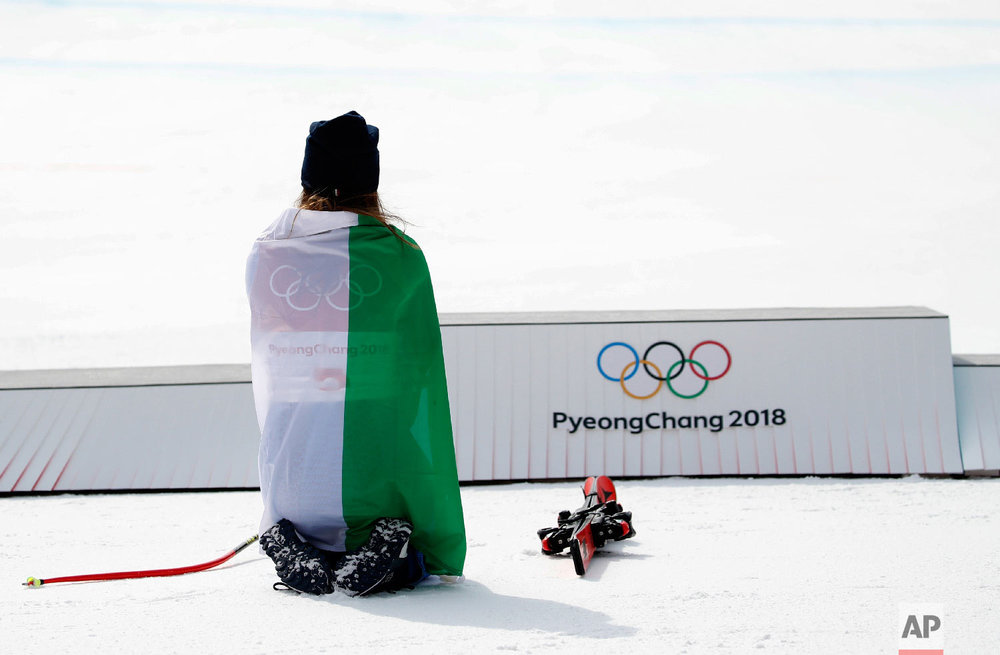 Gold medal winner Sofia Goggia, of Italy, kneels before the podium during the flower ceremony for the women's downhill at the 2018 Winter Olympics in Jeongseon, South Korea, Wednesday, Feb. 21, 2018. (AP Photo/Christophe Ena)