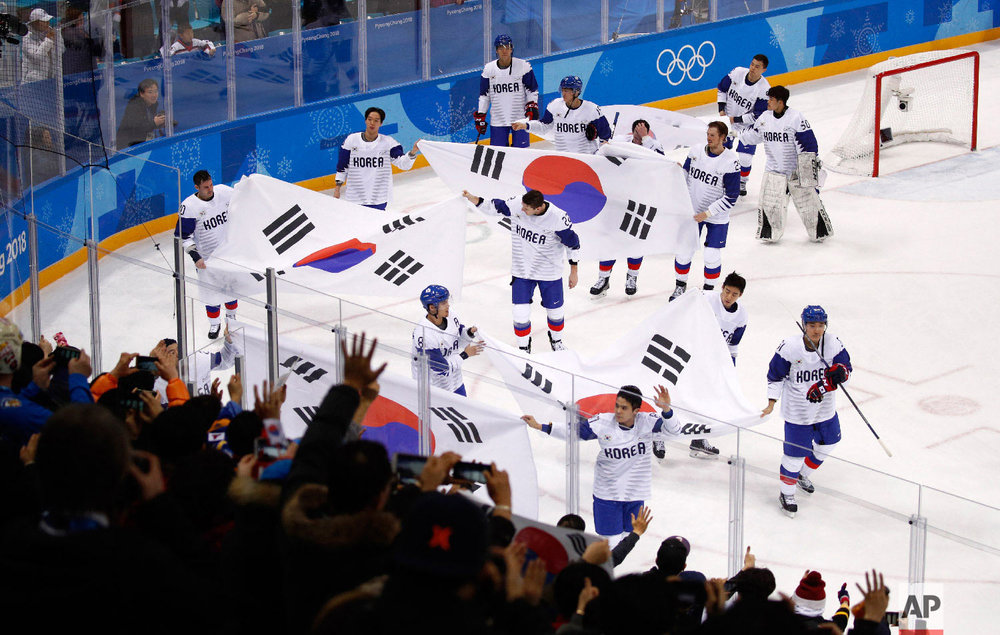 South Korea players wave flags as they skate around after the qualification round of the men's hockey game against Finland at the 2018 Winter Olympics in Gangneung, South Korea, Tuesday, Feb. 20, 2018. Finlandwon 5-2. (AP Photo/Jae C. Hong)