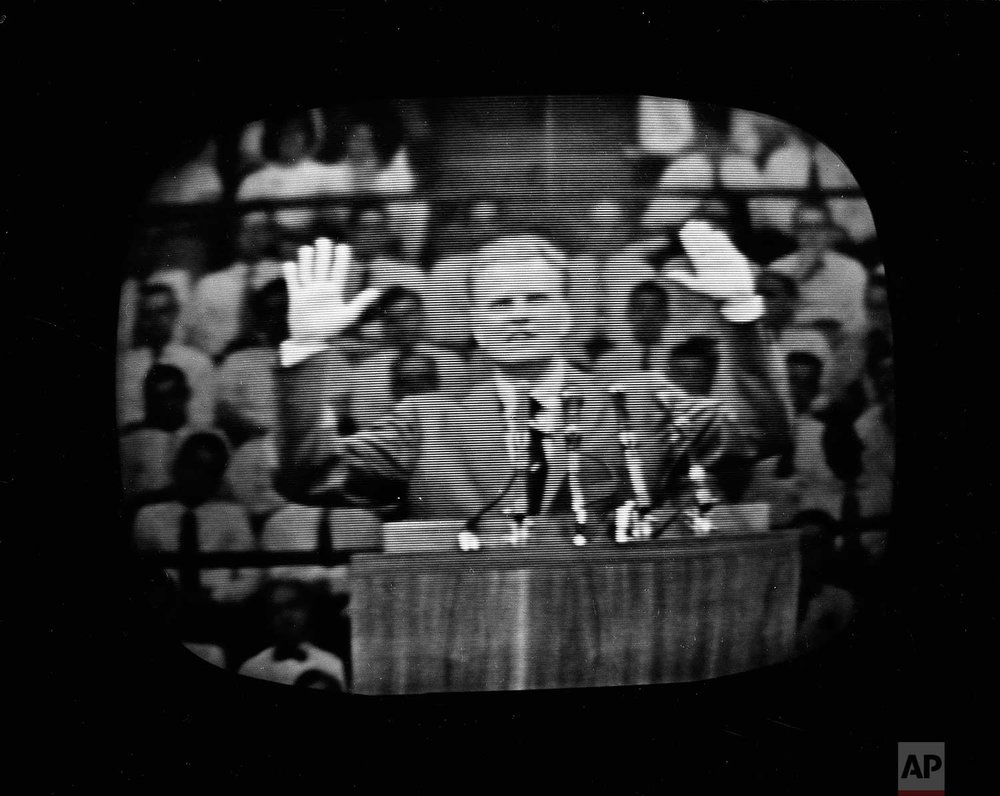 The Rev. Billy Graham appears on a television screen during a live telecast of his crusade at New York's Madison Square Garden, that a standing-room-only crowd of over 19,000 attended, June 1, 1957.  (AP Photo)