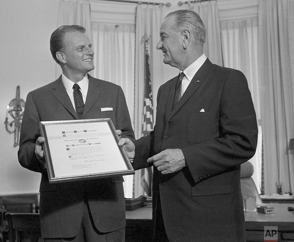 In this May 10, 1966 photo, President Lyndon Johnson presents the Man of the Year award of the Big Brothers organization to evangelist Billy Graham at the White House in Washington. (AP Photo)