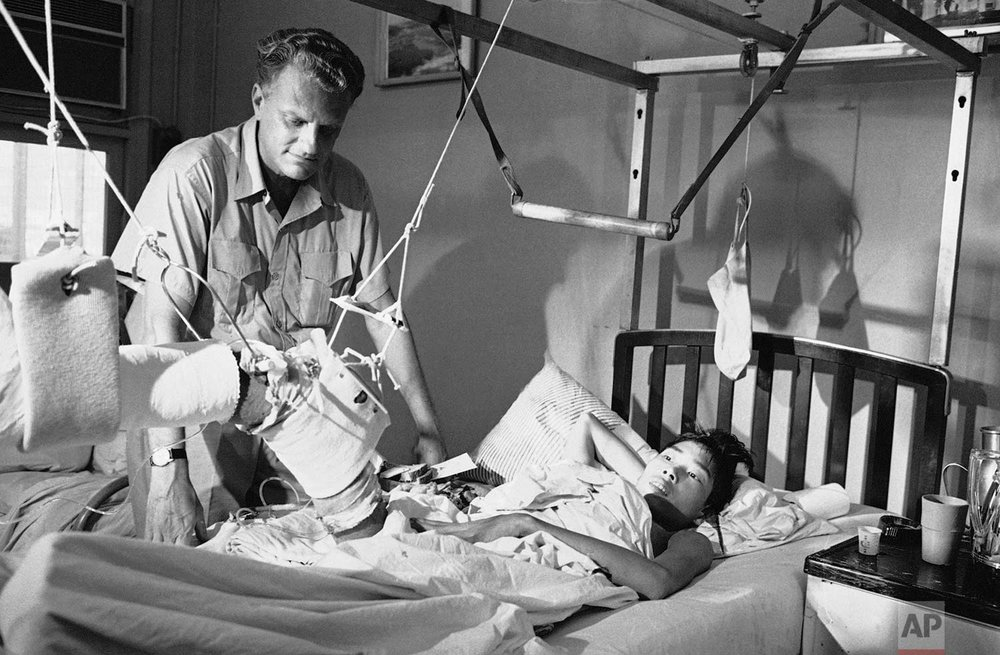 Evangelist Billy Graham looks upon a Viet Cong POW in traction and being treated for battle wounds at the U.S. 3rd Field Hospital in Saigon Dec. 21, 1966. (AP Photo/Henry Huet)