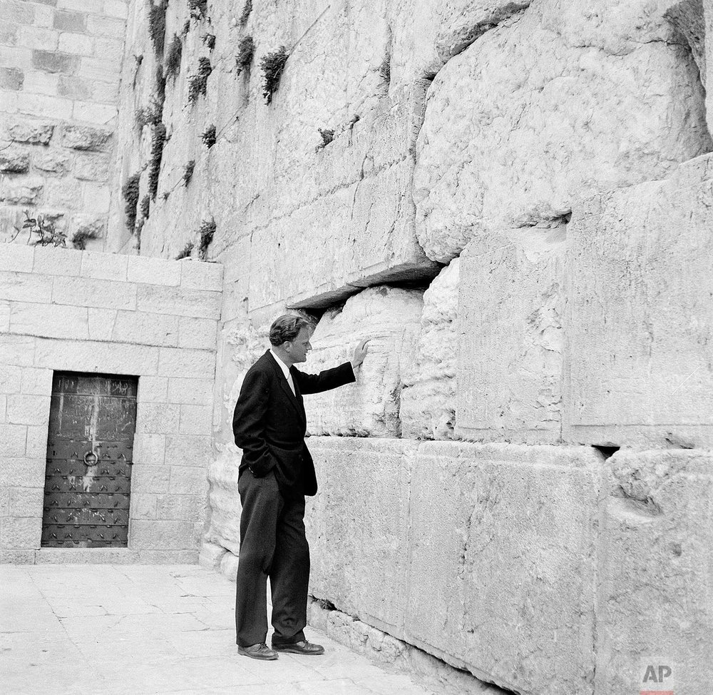 Evangelist Billy Graham stands by the Wailing Wall in Jerusalem, March 17, 1960. (AP Photo/Leila Wynn)