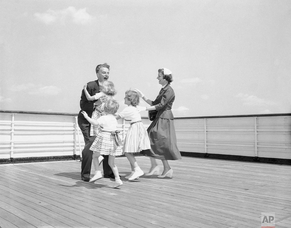 The three young daughters of Billy Graham, North Carolina Evangelist, and his wife, Ruth, rush to greet their father and husband on a deck of the liner Queen Mary following his arrival in New York July 6, 1954, from a five-month preaching tour of Great Britain and Western Europe. Anne, 6, runs into his arms, followed by Ruth, 3, and Virginia, 8. Mrs. Graham joins in the greeting. (AP Photo/Anthony Camerano )
