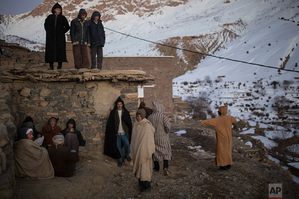 In this Wednesday, Feb. 14, 2018 photo, Berber villagers gather in the evening sun in Tighanmin, a Middle Atlas village near Azilal, central Morocco. (AP Photo/Mosa'ab Elshamy)