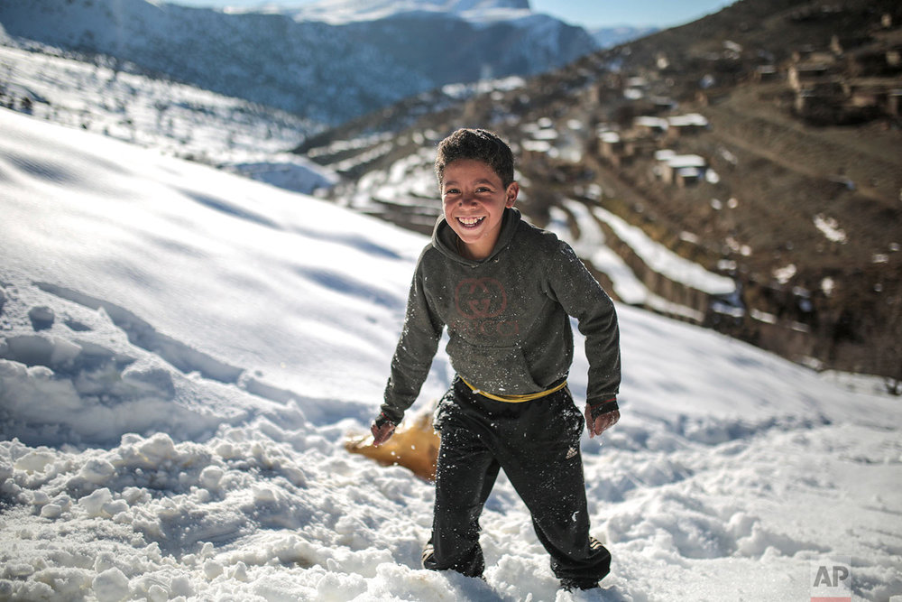 In this Wednesday, Feb. 14, 2018 photo, Mouhcine, 11, enjoys sledging on snow covered mountains in Tighanmin, a Middle Atlas village near Azilal, central Morocco. (AP Photo/Mosa'ab Elshamy)