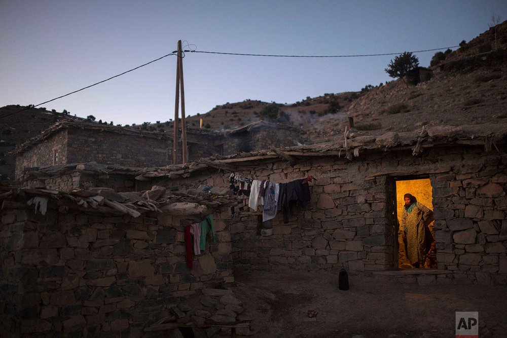 In this Wednesday, Feb. 14, 2018 photo, a woman waits for her family as she prepares dinner in Tighanmin, a Middle Atlas village near Azilal, central Morocco. (AP Photo/Mosa'ab Elshamy)