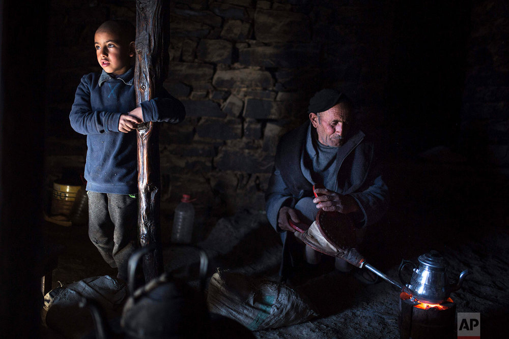 In this Wednesday, Feb. 14, 2018 photo, Mostfa Oulhassan, 68, prepares tea for his family inside his home in Tighanmin, a Middle Atlas village near Azilal, central Morocco.(AP Photo/Mosa'ab Elshamy)