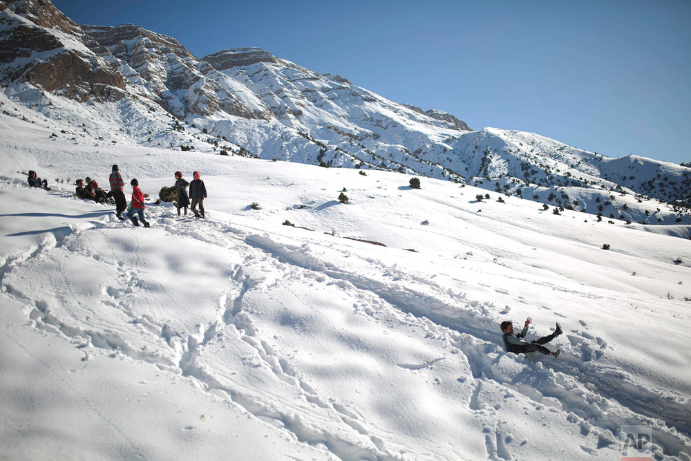 In this Wednesday, Feb. 14, 2018 photo, children enjoy sledging after school on snow covered mountains in Tighanmin, a Middle Atlas village near Azilal, central Morocco. (AP Photo/Mosa'ab Elshamy)