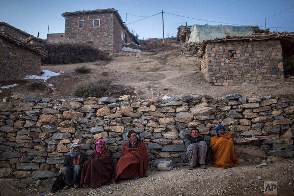 In this Wednesday, Feb. 14, 2018 photo, Berber villagers gather for warmth in the evening sun in Tighanmin, a Middle Atlas village near Azilal, central Morocco.(AP Photo/Mosa'ab Elshamy)