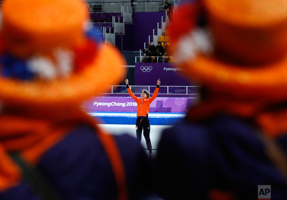 Dutch supporters watch as gold medalist Esmee Visser of The Netherlands celebrates on the podium after the women's 5,000 meters speedskating race at the Gangneung Oval at the 2018 Winter Olympics in Gangneung, South Korea, Friday, Feb. 16, 2018. (AP Photo/Petr David Josek)