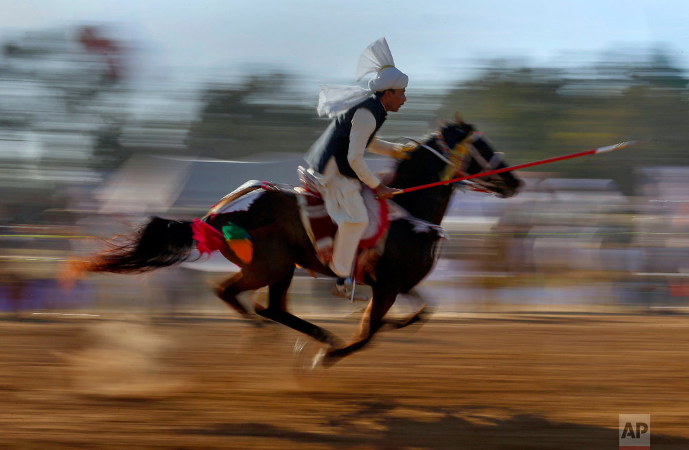 A Pakistani rider races to target a wooden peg during a tent pegging competition organized by the Pakistan Sports Board, in Islamabad, Pakistan, Sunday, Feb. 18, 2018. In the ancient game of tent pegging, a horseman gallops and uses a sword or a lance to pierce, pick up, and carry away a wooden peg. (AP Photo/Anjum Naveed)