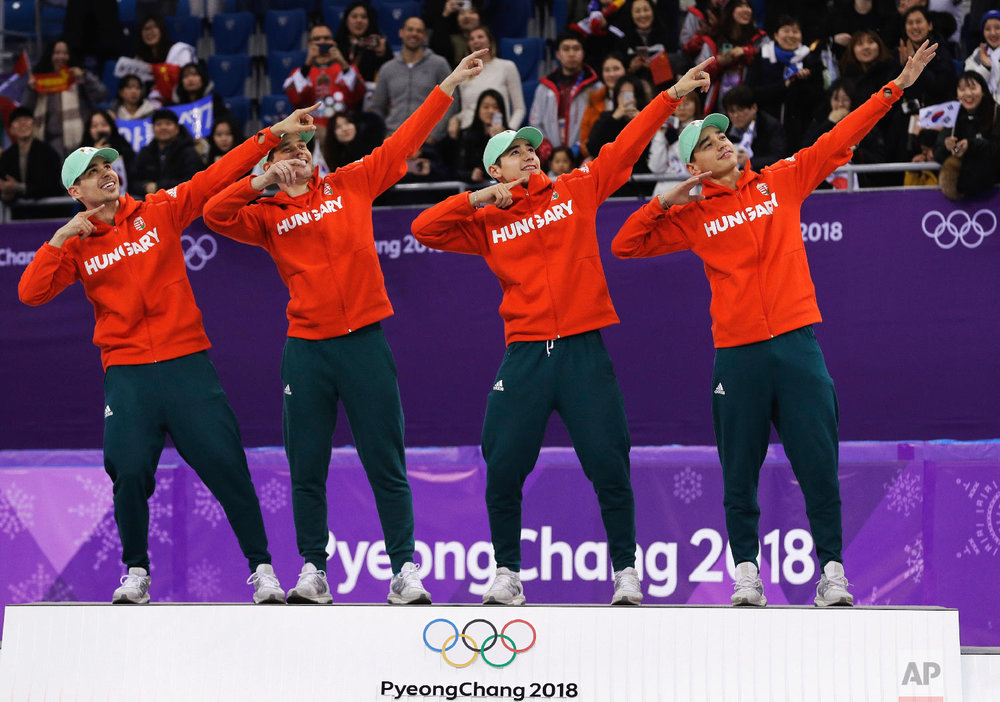 Hungary men's 5000 meters short track speedskating relay final team, from left, Csaba Burjan, Viktor Knoch, Liu Shaoang and Liu Shaolin Sandor celebrate on the podium after winning the gold medal in the Gangneung Ice Arena at the 2018 Winter Olympics in Gangneung, South Korea, Thursday, Feb. 22, 2018. (AP Photo/David J. Phillip)