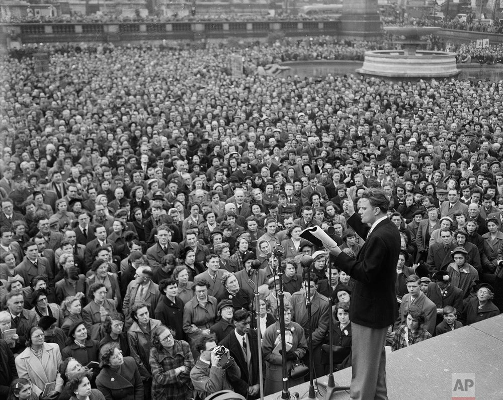 American evangelist Billy Graham reads passages from the Bible to a large, rapt audience in Trafalgar Square, London, April 12, 1954. (AP Photo)