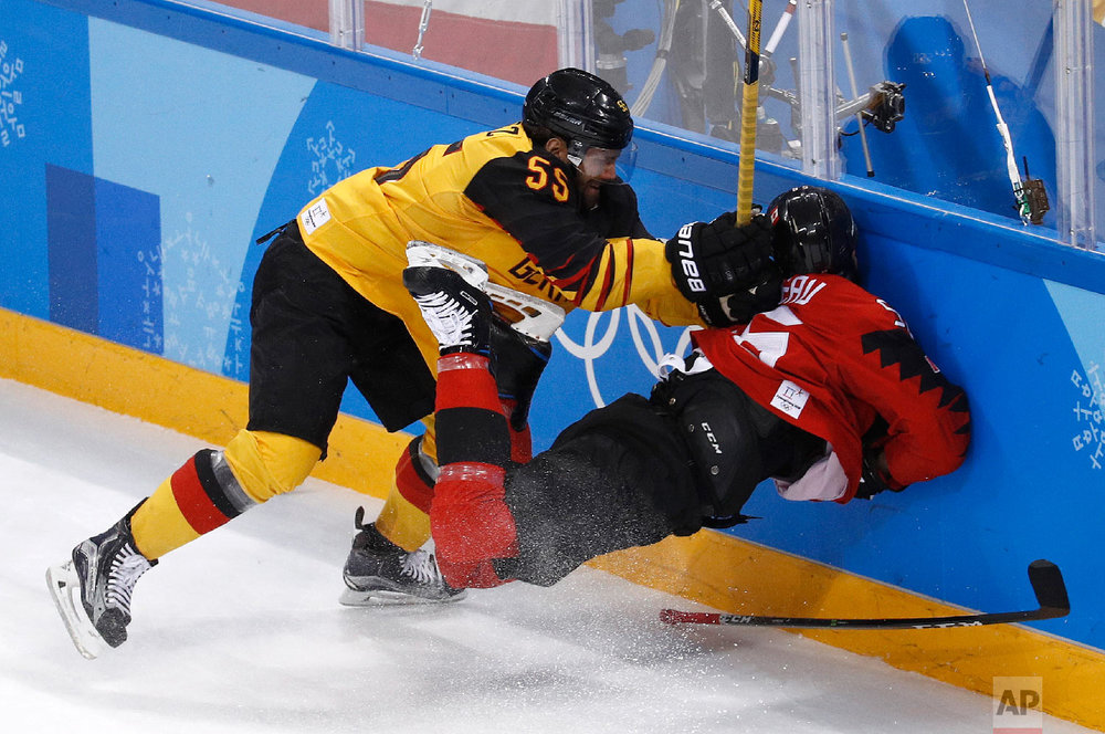 Felix Schutz (55), of Germany, slams Maxim Noreau (56), of Canada, into the wall during the first period of the semifinal round of the men's hockey game at the 2018 Winter Olympics in Gangneung, South Korea, Friday, Feb. 23, 2018. (AP Photo/Patrick Semansky)