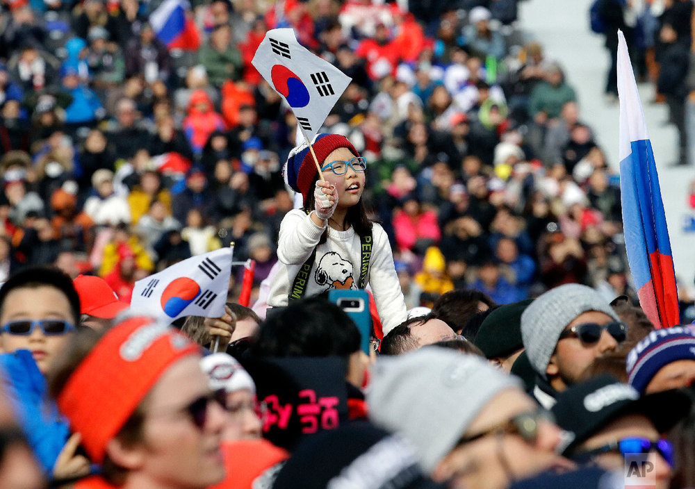 A fan of silver medal winner Lee Sangho, of South Korea, waves a Korean flag during the men's parallel giant slalom semifinal at Phoenix Snow Park at the 2018 Winter Olympics in Pyeongchang, South Korea, Saturday, Feb. 24, 2018. (AP Photo/Lee Jin-man)