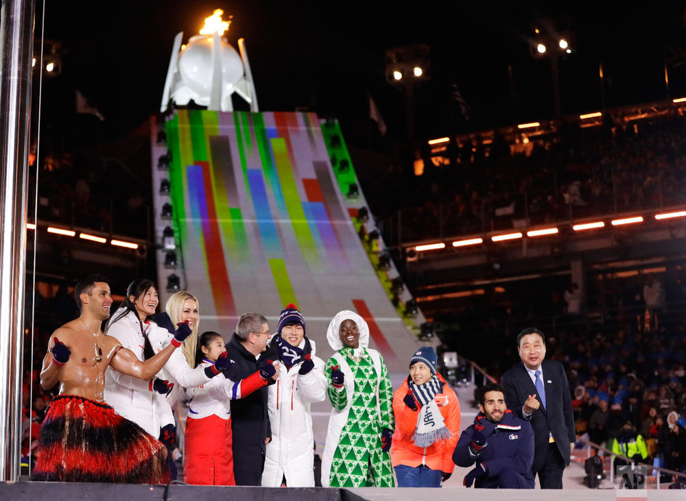 Athletes from various nations including Pita Taufatofua, of Tonga, at left, United States' Lindsey Vonn, third from left, and Thomas Bach, president of the International Olympic Committee, fifth from left, pose during the closing ceremony of the 2018 Winter Olympics in Pyeongchang, South Korea, Sunday, Feb. 25, 2018. (AP Photo/Kirsty Wigglesworth)
