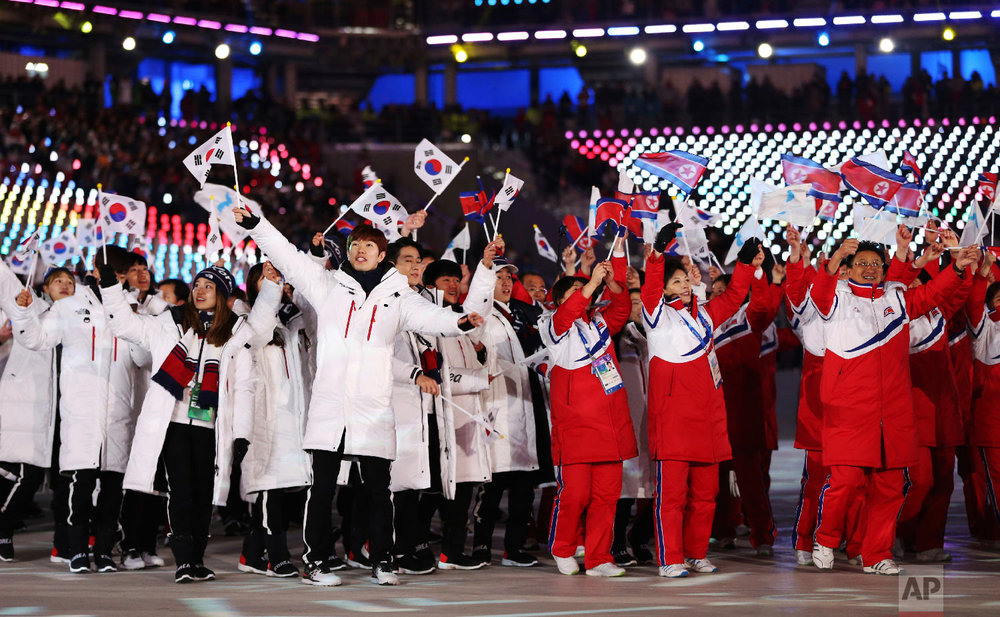 North and South Koreans wave flags during the closing ceremony of the 2018 Winter Olympics in Pyeongchang, South Korea, Sunday, Feb. 25, 2018. (AP Photo/Natacha Pisarenko)