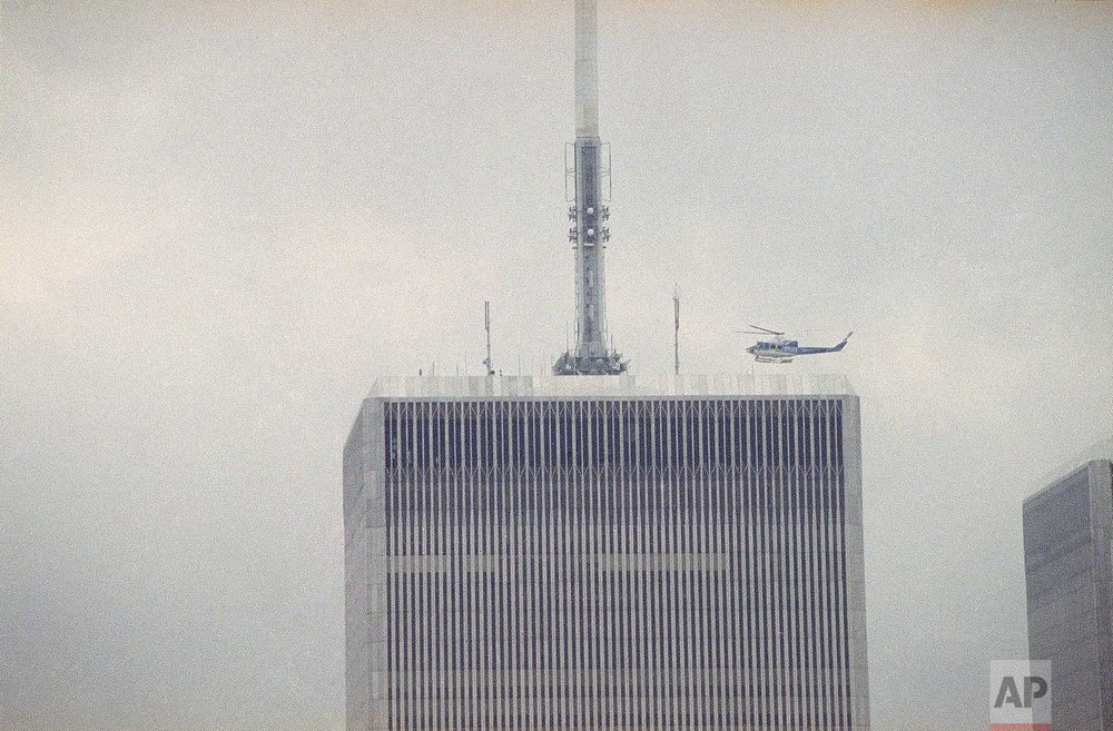 A helicopter readies to land atop one of the twin towers of the World Trade Center in New York, following an explosion in an underground parking garage at the facility, Feb. 26, 1993. (AP Photo/Val Mazzucca)