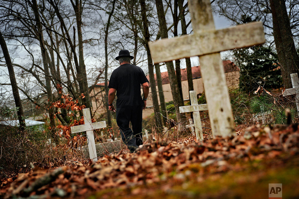 Tyrone Brooks, a veteran civil rights activist, walks through a historic African American cemetery where unknown graves are marked with white crosses and where one of the 1946 lynching victims is buried in Monroe, Ga., Thursday, Feb. 22, 2018. (AP Photo/David Goldman)