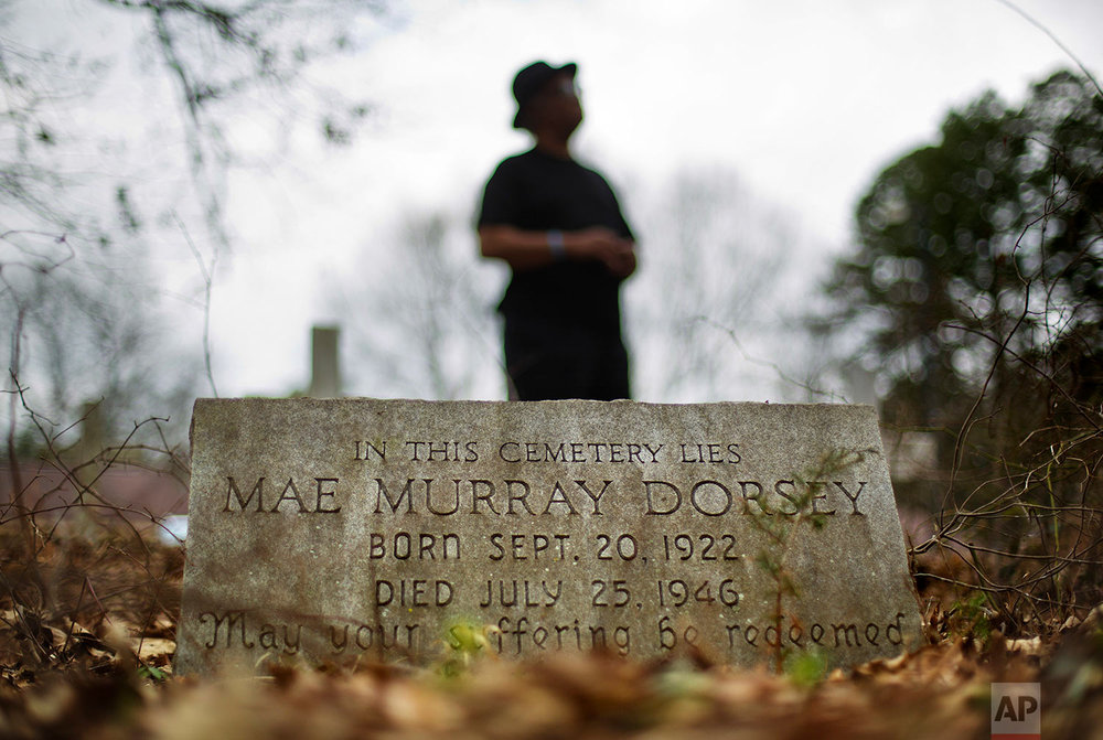 Tyrone Brooks, a veteran civil rights activist, stands behind the tombstone of Mae Murray Dorsey who was killed in a 1946 lynching by a white mob in Monroe, Ga., Thursday, Feb. 22, 2018. (AP Photo/David Goldman)