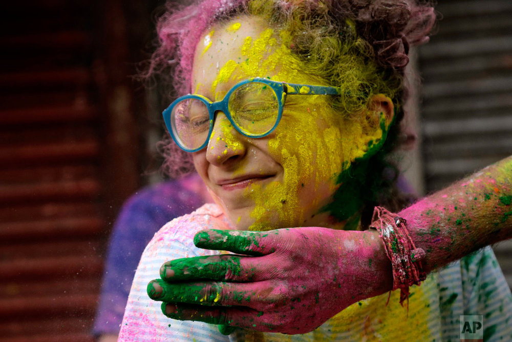 A tourist has powder smeared on her face during Holi in Kolkata, India, March 1, 2018. (AP Photo/Bikas Das)