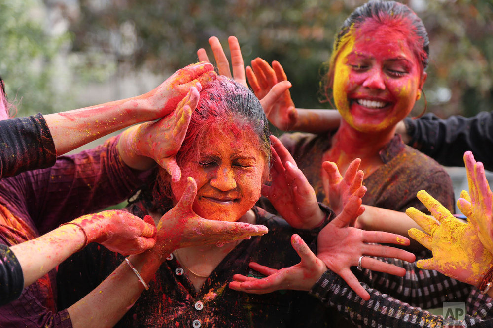 Girls smear colored powder during Holi March 1, 2018. (AP Photo/Channi Anand)