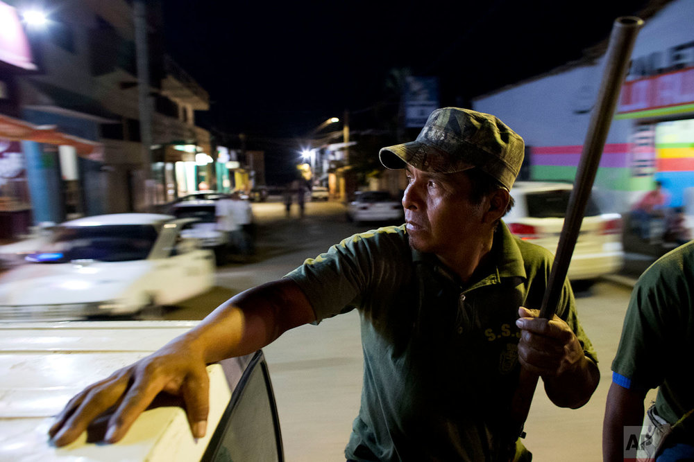 "In this Feb. 7, 2018 photo, ""community police"" vigilante Rene Zeferino rides in the back of a pickup as his unit patrols the streets of Ayutla de los Libres, in the Mexican state of Guerrero. (AP Photo/Rebecca Blackwell)"
