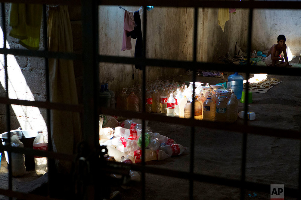 "In this Feb. 4, 2018 photo, a young man being held by the ""community police"" vigilante force sits in an abandoned building turned into a makeshift cell for non-violent offenders, alongside bottles of river water used for bathing, in Ayutla de los Libres, in the Mexican state of Guerrero. (AP Photo/Rebecca Blackwell)"