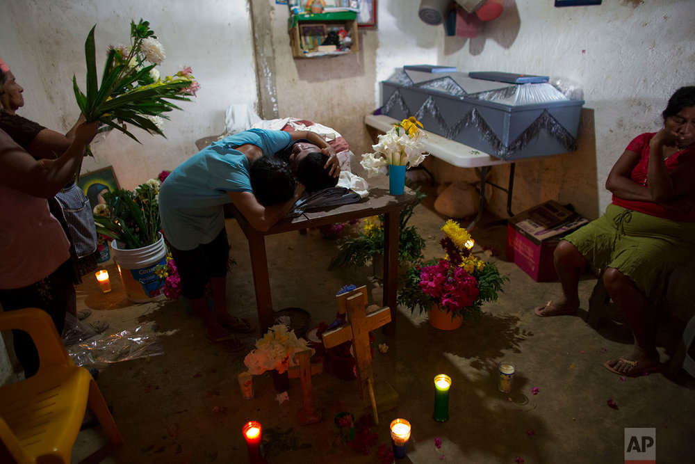"In this Feb. 8, 2018 photo, Maribel Julio Meneses weeps over the body of her son Daniel Julio Julio, a ""community police"" vigilante who was ambushed and killed in the village of Huamuchapa, near Tecoanapa, in the Mexican state of Guerrero. (AP Photo/Rebecca Blackwell)"