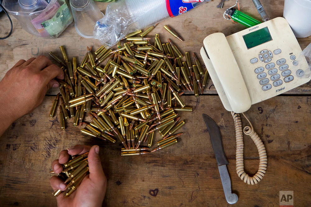 "In this Feb. 8, 2018 photo, a ""community police"" vigilante counts rifle bullets at his base, in Buenavista de la Salud, in the Mexican state of Guerrero. (AP Photo/Rebecca Blackwell)"