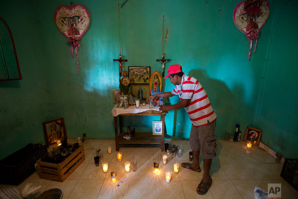 "In this Feb. 5, 2018 photo, a family member adjusts an altar set up in honor of Alexis Estrada Asencio, in La Concepcion, in the Mexican state of Guerrero. Asencio, a 17-year-old bull-riding enthusiast, was allegedly killed in January along with five other civilians by members of the ""community police"" vigilante force. (AP Photo/Rebecca Blackwell)"