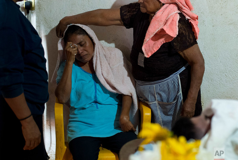"In this Feb. 8, 2018 photo, Maribel Julio Meneses is comforted by relatives during the wake for her son Daniel Julio Julio, a ""community police"" vigilante who was ambushed and killed in the village of Huamuchapa, near Tecoanapa, in the Mexican state of Guerrero state. (AP Photo/Rebecca Blackwell)"