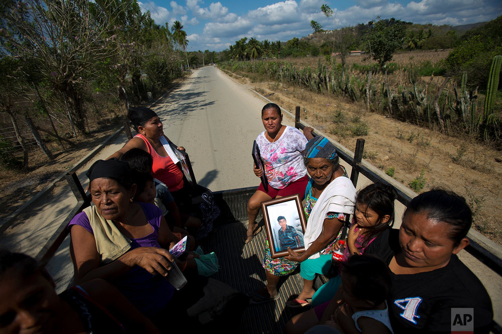"In this Feb. 5, 2018 photo, family members of civilians allegedly killed by ""community police"", ride home holding photographs of their deceased loved ones, in La Concepcion, in the Mexican state of Guerrero. The women were returning from meeting with reporters at the town council building where they say their relatives were killed in a confrontation between vigilante forces and other townsfolk. (AP Photo/Rebecca Blackwell)"