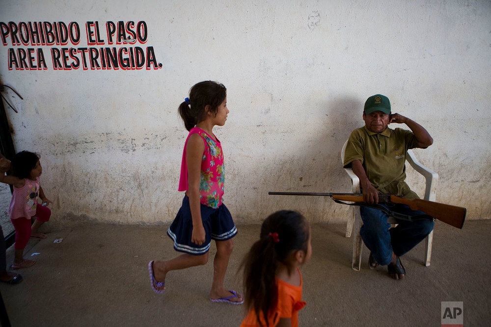 "In this Feb. 4, 2018 photo, children walk past a ""community police"" vigilante at the  force's base, in Ayutla de los Libres, in the Mexican state of Guerrero. (AP Photo/Rebecca Blackwell)"