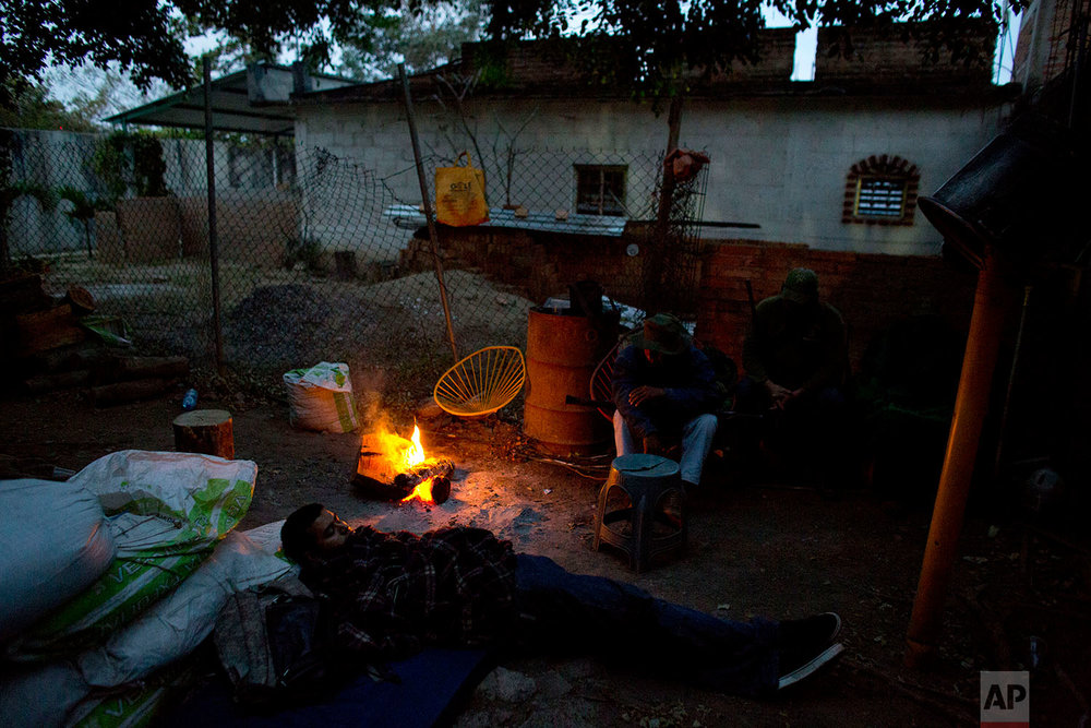 "In this Feb. 9, 2018 photo, ""community police"" vigilantes gather around a campfire just after dawn as they pass a cold night on duty outside their base in Buenavista de la Salud, in the Mexican state of Guerrero. (AP Photo/Rebecca Blackwell)"