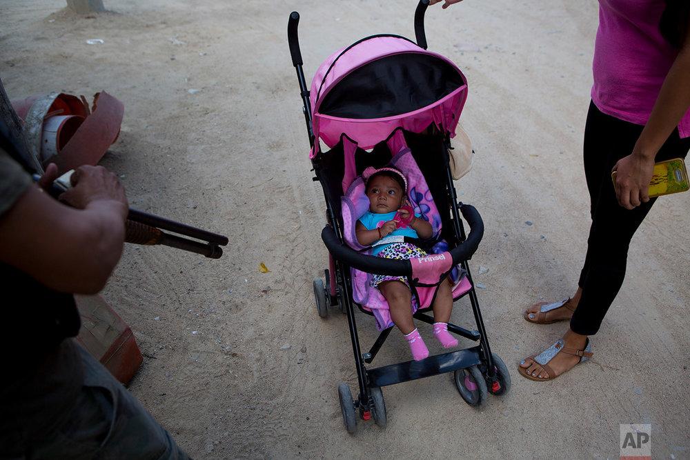 "In this Feb. 6, 2018 photo, a baby peers up at a ""community police"" vigilante, in Xaltianguis, in the Mexican state of Guerrero. (AP Photo/Rebecca Blackwell)"