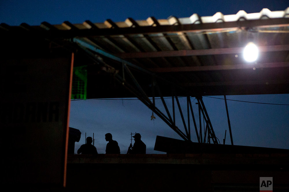 "In this Feb. 8, 2018 photo, ""community police"" are silohoiuteed against an evening sky as they stand guard on the roof of the vigilantes force's base in Buenavista de la Salud, in the Mexican state of Guerrero. (AP Photo/Rebecca Blackwell)"