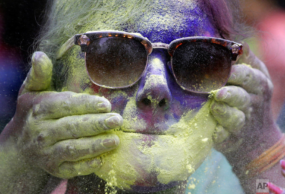 A women celebrates Holi, in Mumbai, India, March. 2, 2018. (AP Photo/Rajanish Kakade)