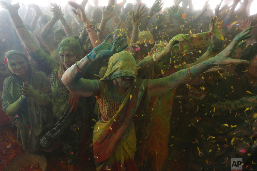 Indian Hindu devotees dance amid colored powder and flowers thrown on them during Holi festival celebration at the Lord Jagannath temple in Ahmadabad, India, Friday, March 2, 2018. (AP Photo/Ajit Solanki)