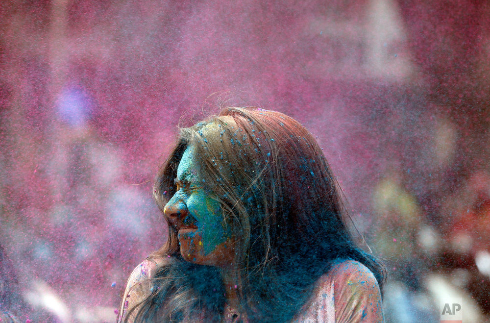 An Indian girl's face is smeared in color as she celebrates Holi, the Hindu festival of colors, in Mumbai, India, Friday, March. 2, 2018. (AP Photo/Rajanish Kakade)
