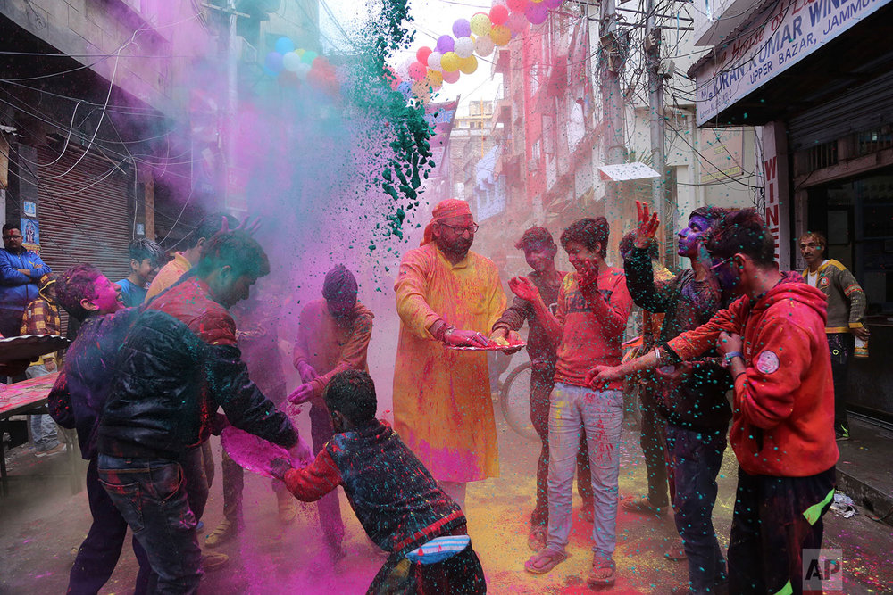 Indians play with colored powder during Holi festival celebrations in Jammu, India, Thursday, March 1, 2018. Holi, the Hindu festival of colors, also heralds the coming of spring. (AP Photo/Channi Anand)