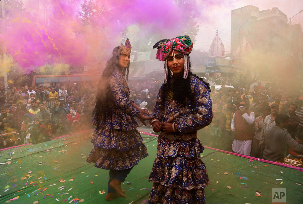 Indians dressed as Hindu deities Radha, center, and Krishana play Holi in Jammu, India, Thursday March 1, 2018.  (AP Photo/Channi Anand)