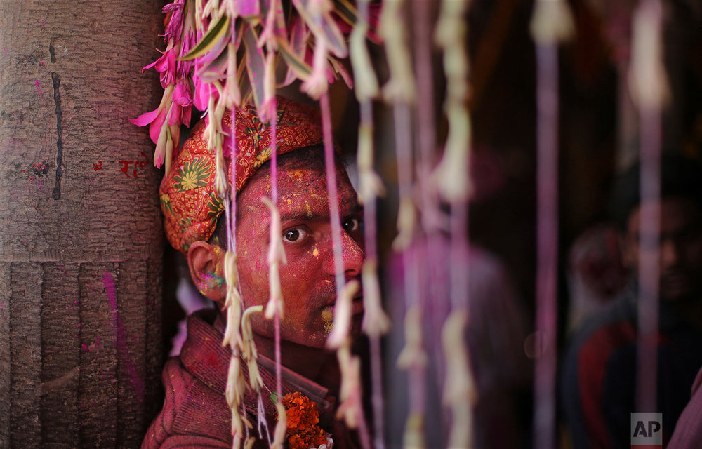 A Hindu devotee, with his face smeared with colors, rests at the Ladali or Radha temple, before the procession for the Lathmar Holi festival, the legendary hometown of Radha, consort of Hindu God Krishna, in Barsana, India, Saturday, Feb. 24, 2018. (AP Photo/Altaf Qadri)
